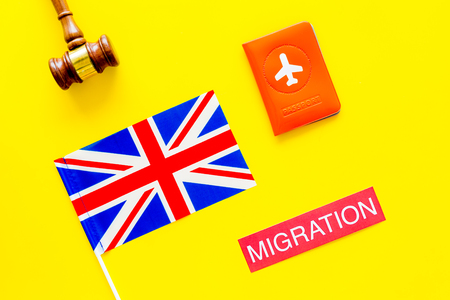 Immigration to Britain concept. Text immigration near passport cover and british flag, hammer on yellow background top view