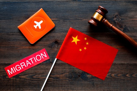 Immigration to China concept. Text innigration near passport cover and chinese flag, judge hammer on dark wooden background top view