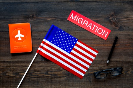 Immigration to United States of America concept. Textimmigration near passport cover and USA flag on dark wooden background top view