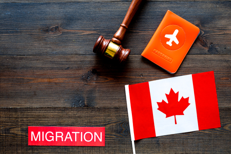 Immigration to Canada concept. Text immigration near passport cover and canadian flag, hammer on dark wooden background top view space for text Фото со стока