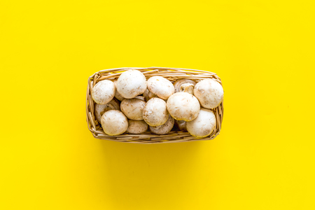 Mushroom champignons. Fresh raw whole champignons in basket on yellow background top view copy space