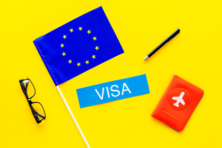 Schengen visa. Visa to Europe concept. Text visa near passport cover and european flag on yellow background top view