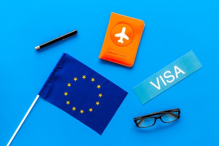 Schengen visa. Visa to Europe concept. Text visa near passport cover and european flag on blue background top view