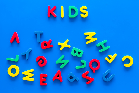Early childhood development concept. Word kids written by plastic letters of toy alphabet on blue background top view 写真素材