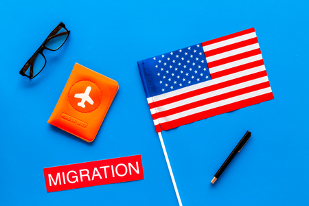 Immigration to United States of America concept. Textimmigration near passport cover and USA flag on blue background top view 版權商用圖片