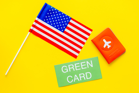 United States of America permanent resident cards. Immigration concept. Text green card near passport cover and US flag top view on yellow background copy space Stock fotó