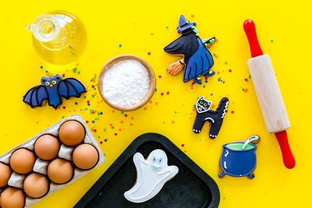 Make halloween gingerbread concept. Icing cookies near rolling pin, baking sheet, eggs, flour on yellow background top view