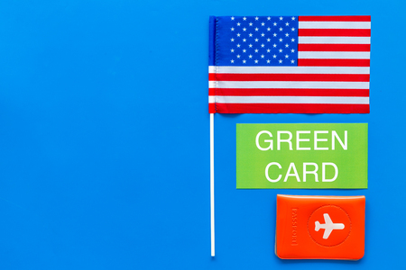 Green card text near passport cover and USA flag top view on blue background copy space. Immigration to United states of america