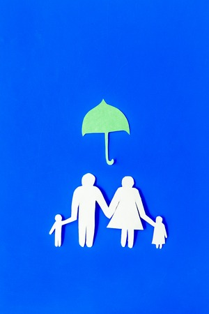 Illustration of social security concept. Financial protection. Family silhouette, cutout under umbrella on blue background top view copy space Standard-Bild