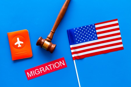 Immigration to United States of America concept. Textimmigration near passport cover and USA flag, judge hammer on blue background top view