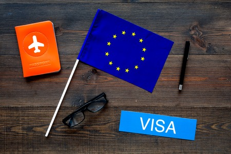 Schengen visa. Visa to Europe concept. Text visa near passport cover and european flag on dark wooden background top view 版權商用圖片