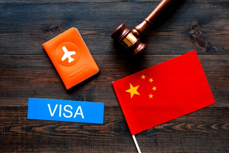 Visa to China concept. Text visa near passport cover and chinese flag. judge hammer on dark wooden background top view 版權商用圖片