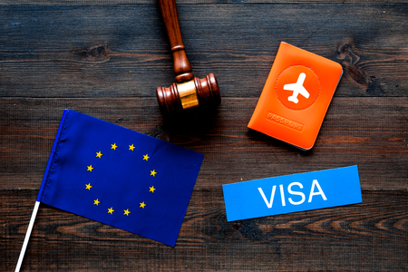 Schengen visa. Visa to Europe concept. Text visa near passport cover and european flag, judge hammer on dark wooden background top view