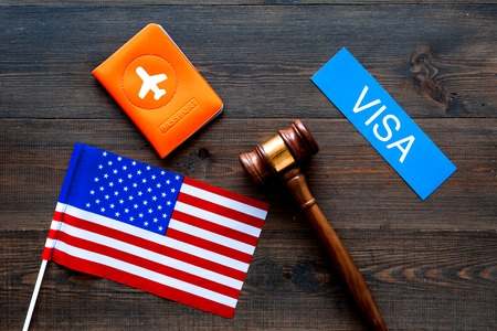 Visa to United States of America concept. Text visa near passport cover and USA flag, judge hammer on wooden background top view.