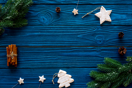 Spruce branch, cones and vintage toys in shape of spruce and stars on blue background for decoration on chrismas or new year top view.