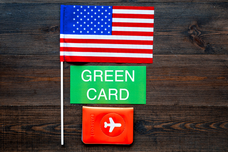 Green card text near passport cover and USA flag top view on dark wooden background copy space. Immigration to United states of america. Banco de Imagens