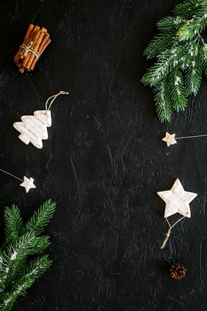 Decoratie voor wintervakantie concept. Kerstmis, Nieuwjaar. Vuren tak, kegels en speelgoed op zwarte achtergrond bovenaanzicht. Stockfoto