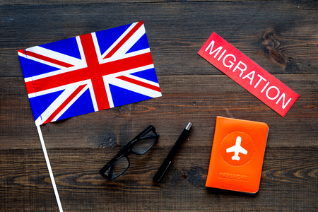 Immigration to Britain concept. Text immigration near passport cover and british flag on dark wooden background top view