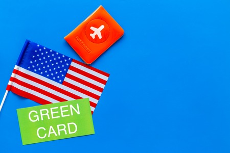 Green card text near passport cover and USA flag top view on blue background copy space. Immigration to United states of America.