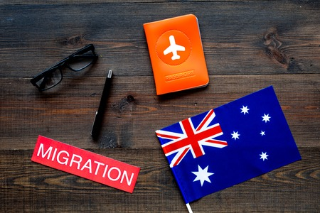 Immigration concept. Text immigration near passport cover and flag.