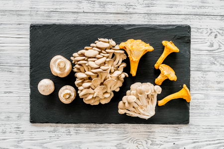 Cook mushrooms concept. Champignons, oysters, chanterelles on cutting board on grey wooden background top view Reklamní fotografie - 110382086