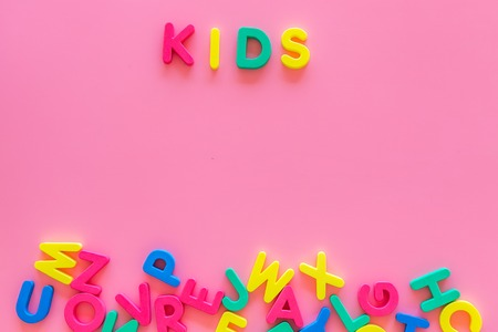 Early childhood development concept. Word kids written by plastic letters of toy alphabet on pink background top view copy space