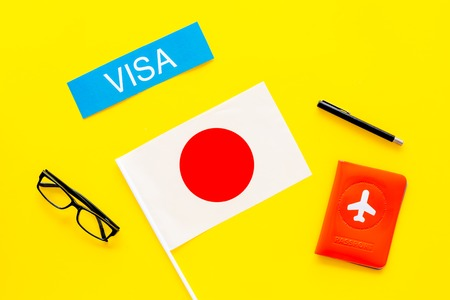 Visa to Japan concept. Text visa near passport cover and japanese flag on yellow background top view 版權商用圖片
