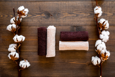 Cotton towels high quality. Set of towels twisted coil near dry cotton flowers on dark wooden background top view Stock fotó