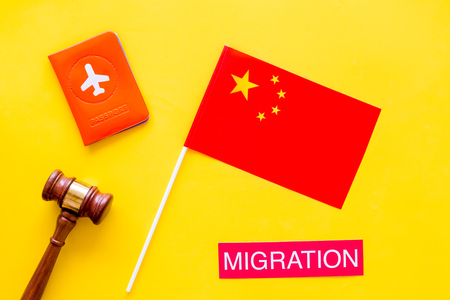 Immigration to China concept. Text innigration near passport cover and chinese flag, judge hammer on yellow background top view