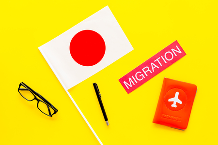 Immigration to Japan concept. Text immigration near passport cover and japanese flag on yellow background top view Фото со стока