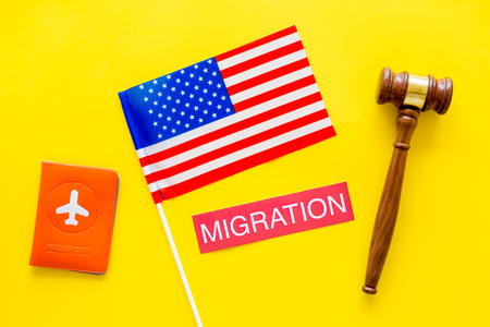 Immigration to United States of America concept. Textimmigration near passport cover and USA flag, judge hammer on yellow background top view Фото со стока
