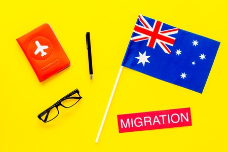 Immigration to Australia concept. Text immigration near passport cover and australian flag on yellow background top view
