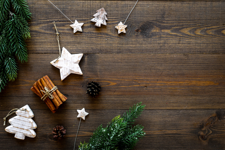 Spruce branch, cones and vintage toys in shape of spruce and stars on dark wooden background for decoration on chrismas or new year top view copy space Stock Photo