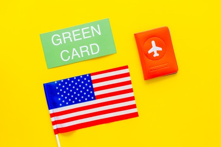 United States of America permanent resident cards. Immigration concept. Text green card near passport cover and US flag top view on yellow background