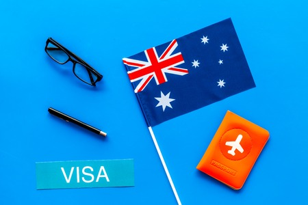 Visa to Australia concept. Text visa near passport cover and australian flag on blue background top view