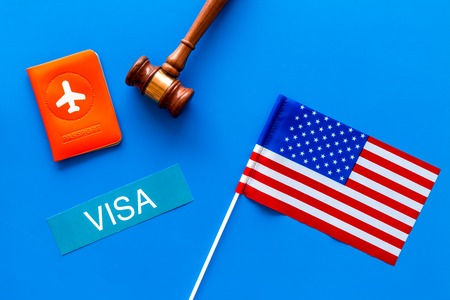 Visa to United States of America concept. Text visa near passport cover and USA flag, judge hammer on blue background top view copy space
