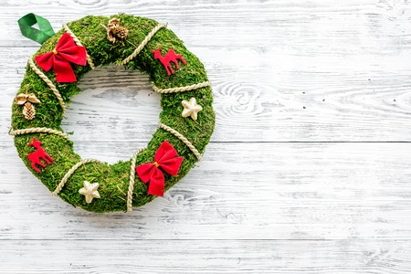 Christmas wreath traditional, classic type. Wreath made of spruce branches and red ribbons on white wooden background top view. Stock Photo