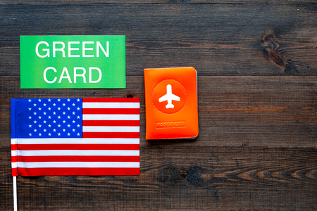 Green card text near passport cover and USA flag top view on dark wooden background copy space. Immigration to United states of america. Фото со стока