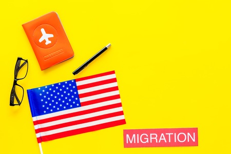 Immigration to United States of America concept. Textimmigration near passport cover and USA flag on yellow background top view. Фото со стока