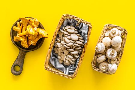 Pilzkonzept kochen. Champignons, Austern, Pfifferlinge im Korb und auf Bratpfanne auf gelbem Hintergrund Draufsicht top