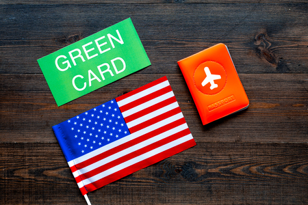 Green card text near passport cover and USA flag top view on dark wooden background. Immigration to United states of america