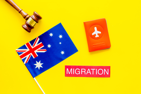Immigration to Australia concept. Text immigration near passport cover and australian flag, hammer on yellow background top view