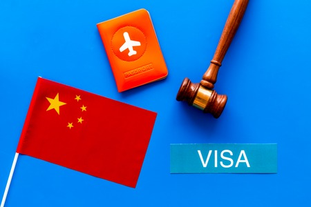 Visa to China concept. Text visa near passport cover and chinese flag. judge hammer on blue background top view Banco de Imagens