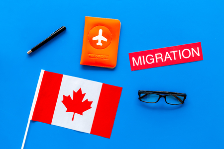 Immigration to Canada concept. Text immigration near passport cover and canadian flag on blue background top view