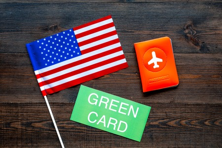 Green card text near passport cover and USA flag top view on dark wooden background. Immigration to United states of america.