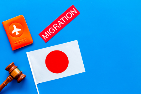 Immigration to Japan concept. Text immigration near passport cover and japanese flag, hammer on blue background top view copy space