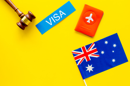 Visa to Australia concept. Text visa near passport cover and australian flag, hammer on yellow background top view copy space