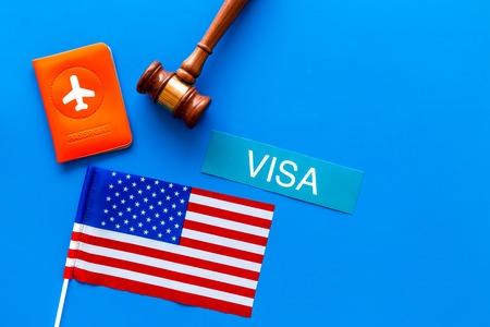 Visa to United States of America concept. Text visa near passport cover and USA flag, judge hammer on blue background top view.