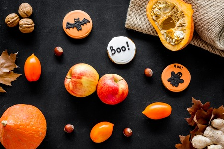 Halloween composition with autumn harvest as dried autumn leaves, pumpkin, apple and cute round hallooween badges with rats, ghousts, Boo text on black background top view pattern