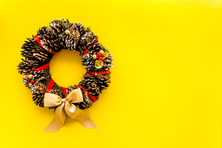 Christmas wreath made of pine cones on yellow background top view.